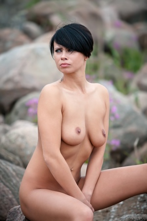 Beautiful nude woman sitting on stones against nature background Stock Photo - 12419252
