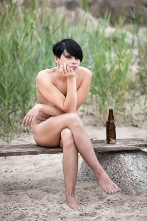 adult nudity: Naked young woman sitting on a bench rests and smokes a cigarette