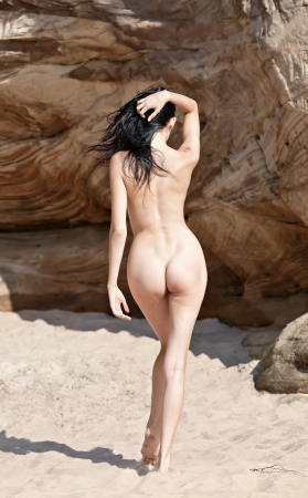 Back view of young naked woman standing in the sand.
