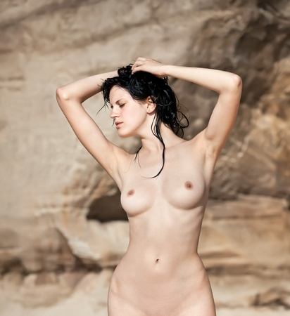 nude woman standing: Sunbathing. Sexy nude woman standing against sandstone background.