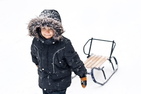 dragging: Winter photo of cute young boy in winter suit pulling snow sledges through the snow