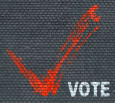 Red painted tick and word Vote on blue brick wall background photo