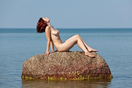 바다 배경에 대해 돌에 앉아 젊은 누드 여자