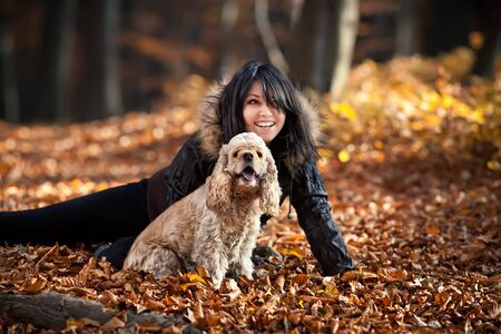 Girl and cocker spaniel in the autumn forest. Focus mainly on the dog photo