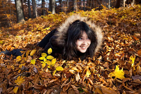Young woman lying in fallen autumn leaves photo