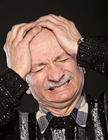 elderly man suffering from a headache photo