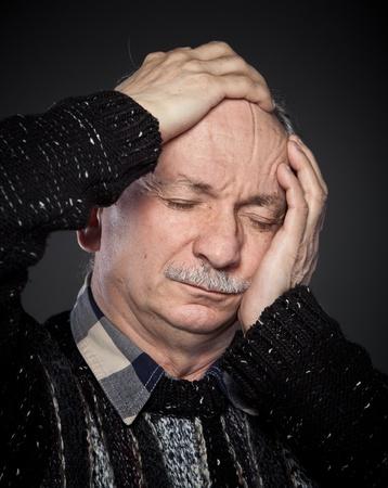 an older man suffering from a headache photo