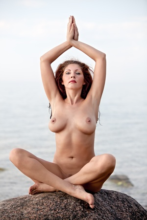 Naked Yoga. Young nude woman sitting on stone on sea background Stock Photo - 12724134