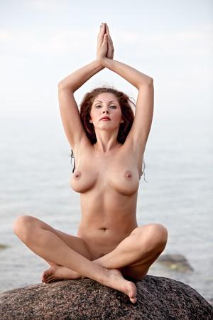 mujer desnuda sentada: Yoga Desnudo. Joven mujer desnuda sentada sobre la piedra en el fondo del mar Foto de archivo