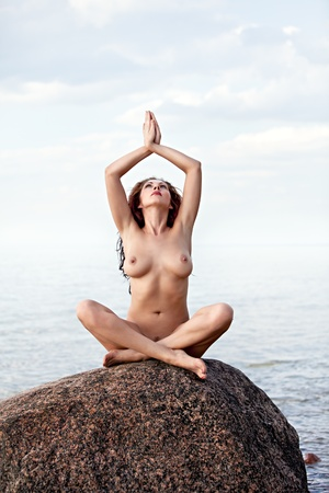 Naked Yoga. Young nude woman sitting on stone on sea background Stock Photo - 12724090
