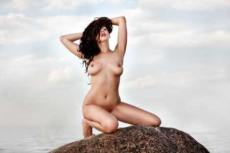 Nude woman kneeling on stone raised her hands on nature background