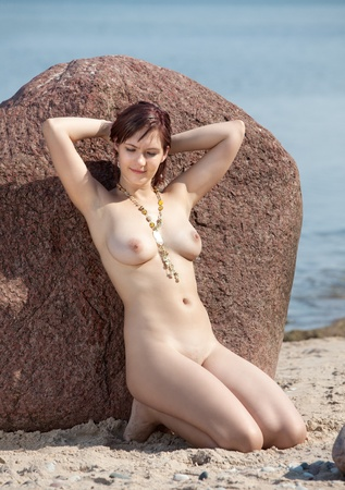 Young naked woman sunbathing near the stone on sea background