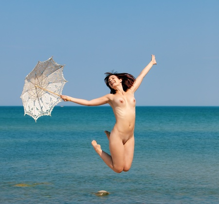 nude outdoors: young nude woman jumping with white umbrella on sea background