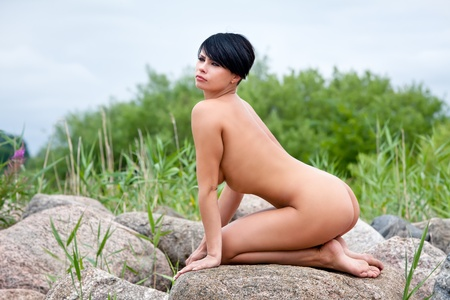 Beautiful nude woman sitting on stones against nature background Stock Photo - 12724288