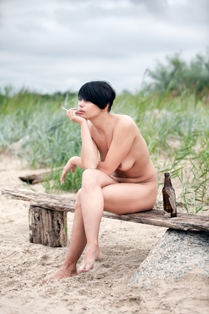 Naked young woman sitting on a bench rests and smokes a cigarette