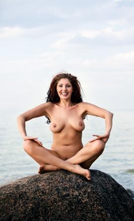 mujer desnuda sentada: Mujer desnuda sentada en una roca contra el fondo del mar y sonriendo Foto de archivo