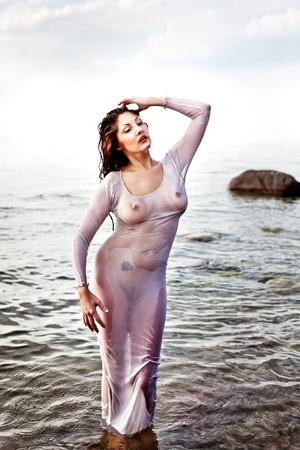 Wet nude woman in a translucent shirt against the sea. Stock Photo - 12724469