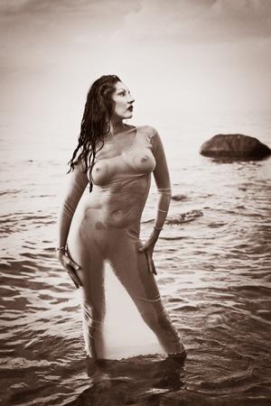wet nude: Una mujer desnuda h�meda con una camisa transparente contra el mar. Estilizaci�n Antiguo foto, grano de la pel�cula a�adido