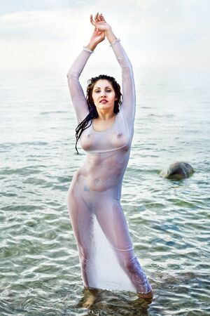 Wet nude woman in a translucent shirt against the sea Stock Photo - 12724486