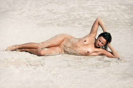 Young wet nude woman lying on the sand