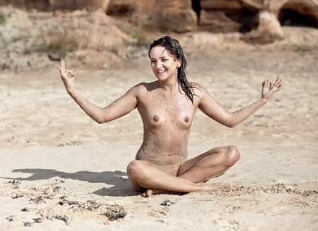 Naked Yoga. Young woman sitting naked on sand Stock Photo - 12729356