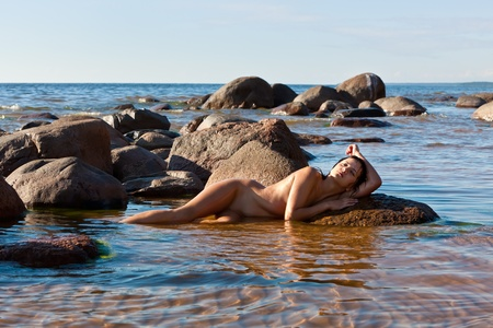 Young nude woman lying on stone  against the sea background Stock Photo - 12720983