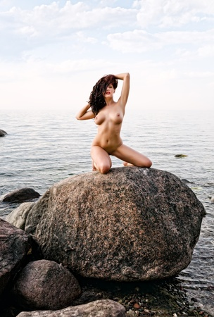 Nude woman kneeling on stone raised her hands on nature background Stock Photo - 12721081