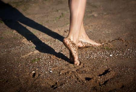 Girl's barefoot legs on the sand beach photo