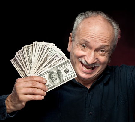 An elderly happyl businessman showing fan of money Stock Photo - 12913797