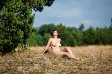 Naked woman sitting on forest glade and sunbathing Stock Photo