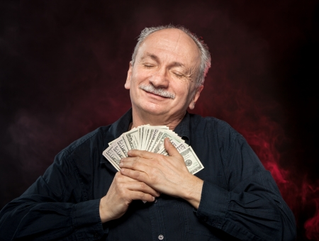 fortunate: Lucky, old man holding with pleasure group of dollar bills Stock Photo