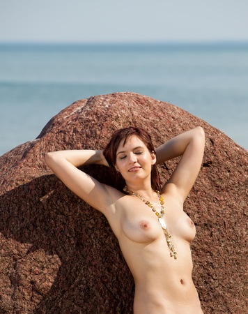 Young naked woman sunbathing near the stone on sea background Stock Photo - 12913939