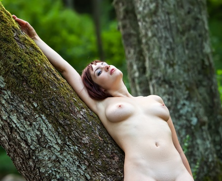 adult nudity: Young nude woman standing near a tree in the forest