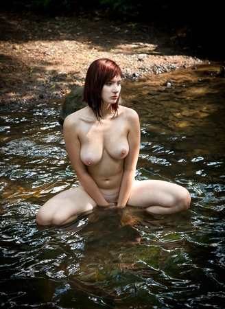 Beautiful naked woman in a forest stream