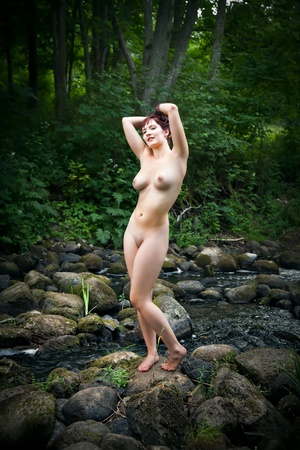 nudity: Young naked woman standing on a stone near the creek in the wood Stock Photo