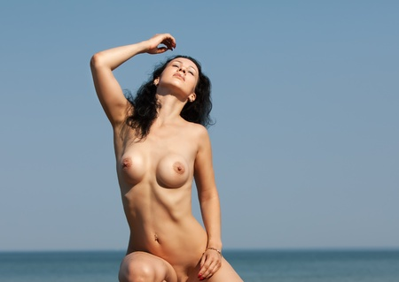 Beautiful nude woman against the sea and blue sky Stock Photo - 13124006