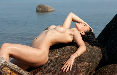 Young nude woman lying on stone  against the sea background Stock Photo
