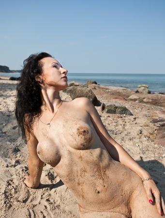 wet nude: Joven mujer desnuda mojada tumbado en la arena contra el fondo del mar Foto de archivo