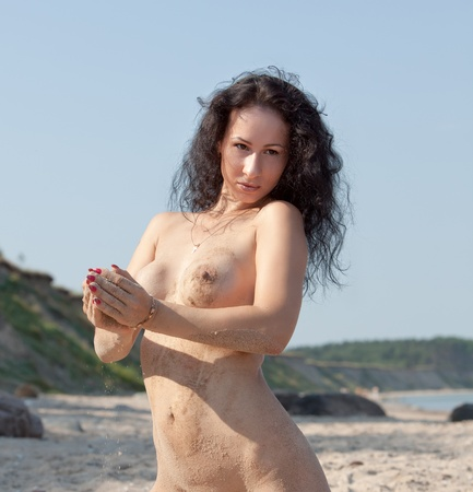 bare breasts: Wet nude woman sunbathing and  playing with sand on the beach Stock Photo