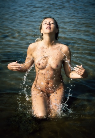 Young nude woman playing with water drops Stock Photo