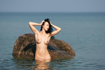 mujer desnuda sentada: Hermosa mujer desnuda sentada sobre una piedra contra el cielo y el azul del mar Foto de archivo