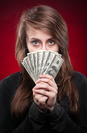 Young woman covering half of face with dollar notes on dark red background photo