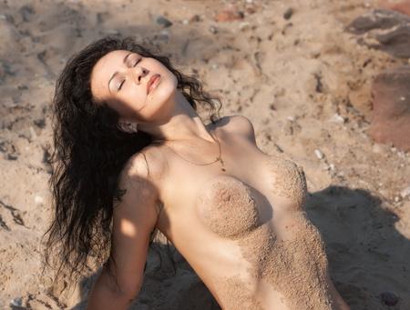wet nude: Joven mujer desnuda h�meda cubierto por la arena tumbado en la playa