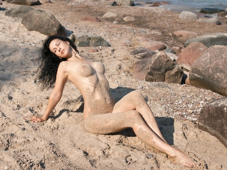 nude outdoors: Young wet nude woman covered by sand lying on the beach Stock Photo