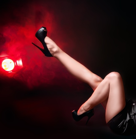 Long  pretty woman legs in shorts with a fashion light