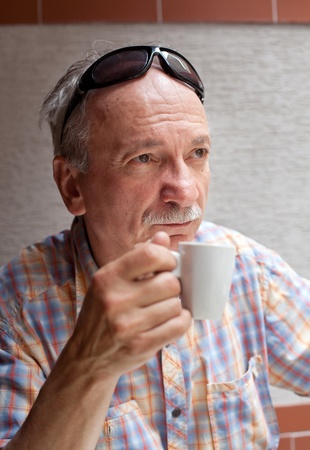 Portrait of smart old man drinking cup of coffee while sitting outside photo
