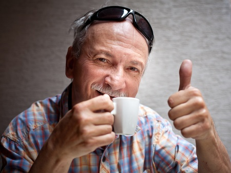 Portrait of smart old man drinking cup of coffee and showing sign OK with fingers photo