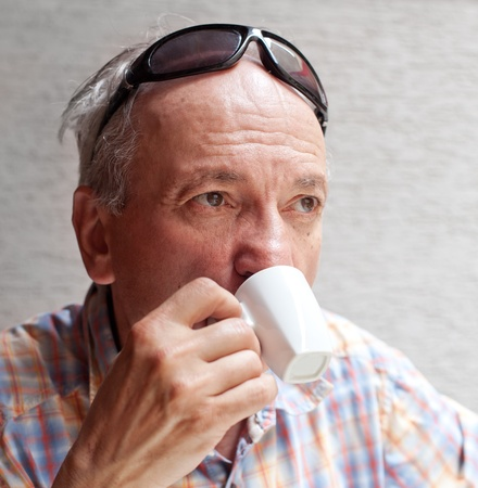 Portrait of smart old man drinking cup of coffee photo