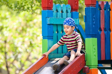 Cute boy in bandana playing on slide photo