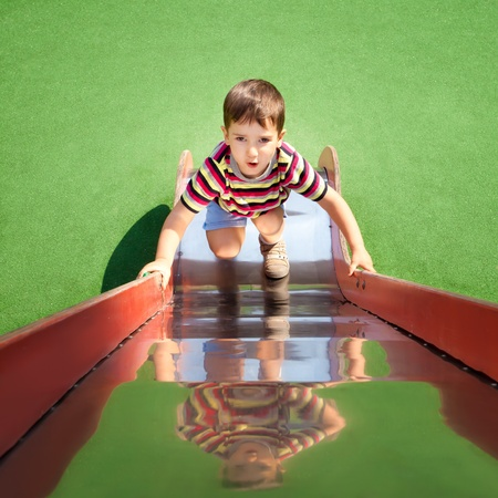 Cute young boy climbing up a slide on playground Stock Photo